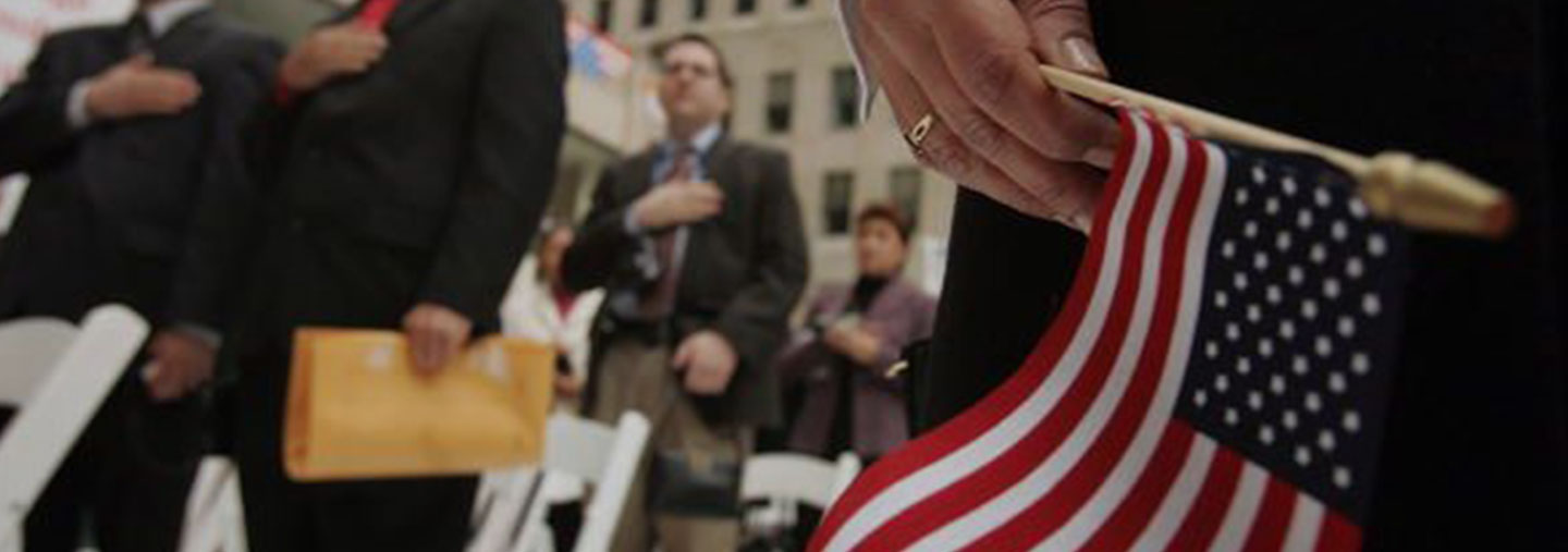 Immigrants with American flag taking citizenship oath