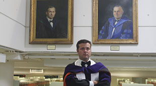 Tanner Stiehl in front of his great-great grandfather and great grandfather's portraits