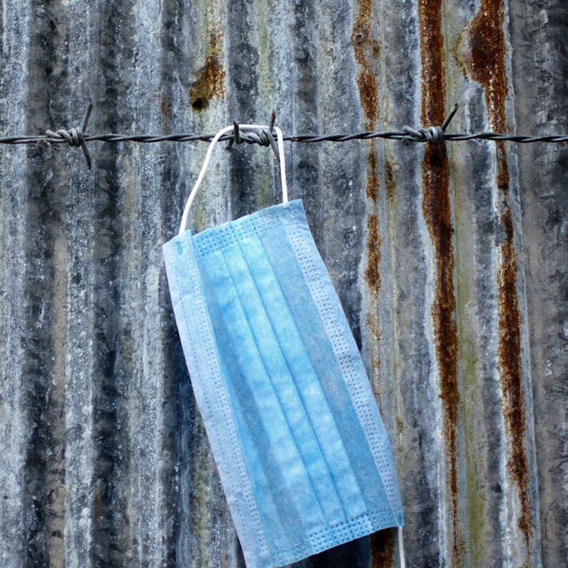 Mask hanging on barbed-wire fence