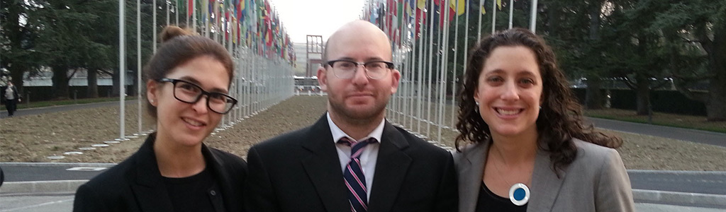 Human Rights Clinic students Charlotte Cassel and James Slater along with Professor Caroline Bettinger-Lopez at the entrance to the United Nations Palais des Naciones in Geneva.